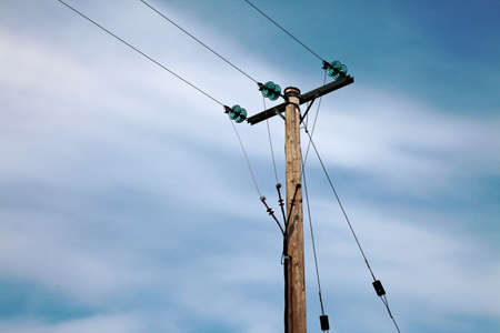 insulators: A wooden electricity pole with green insulators