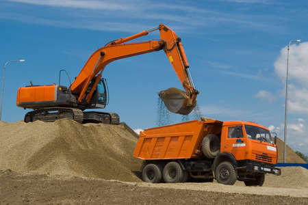 camion volquete: Excavadora y el cami�n en el sitio de construcci�n