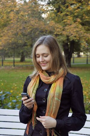 The smiling girl with mobile phone Stock Photo - 2222525