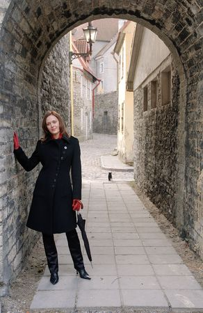 The beautiful girl in a black coat in old narrow street photo