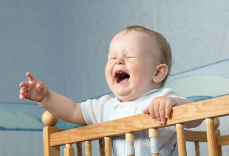 The baby cries and calls mum from a bed Stock Photo
