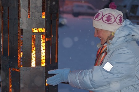 The woman is heated in the winter at a street fireplace Stock Photo - 7684726