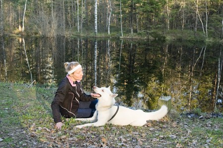 The woman with a dog on the bank of wood lake Stock Photo - 7684867