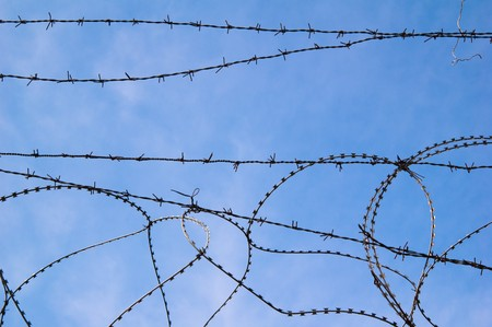 Barbed wire against the blue sky Stock Photo - 7858742