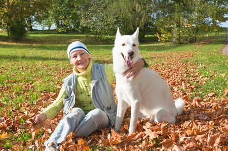 The woman with a white dog in autumn park photo