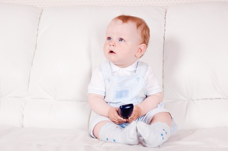 The baby sits on a white sofa with the TV panel Stock Photo - 8103778