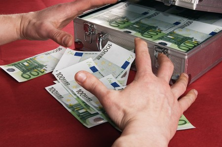 Hands are pulled to a suitcase with money  photo
