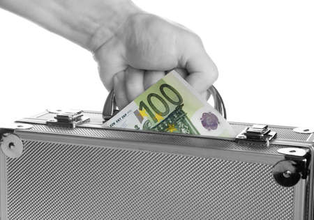 The hand holds a suitcase with money ,isolated on white photo