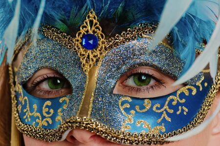 Portrait of the young woman in a carnival to a mask, a close up
