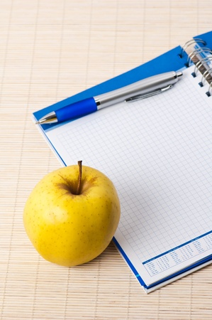 Open notebook, yellow apple and pencil Stock Photo - 8632511