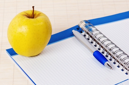 Open notebook, yellow apple and pencil Stock Photo - 8632510