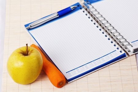 Open notebook, yellow apple and pencil Stock Photo - 8632512