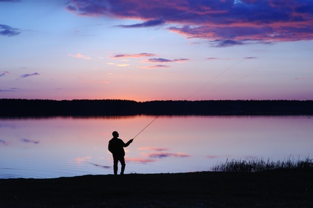Silhouette of the fisher on a background of an evening dawn photo