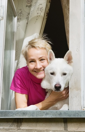 The woman with a white dog look from a window Stock Photo - 8642375
