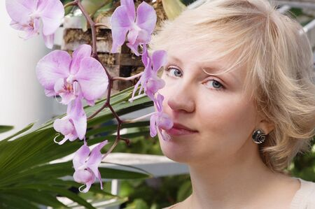smells: The girl smells an orchid