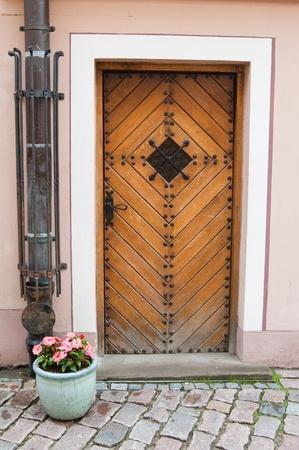Antigua puerta y jarrón con flores Foto de archivo