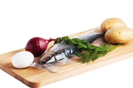 Vegetables and a salty herring on a kitchen board Stock Photo - 12631920