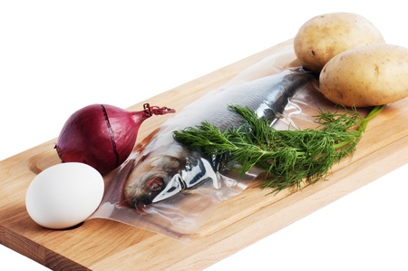 Vegetables and a salty herring on a kitchen board photo