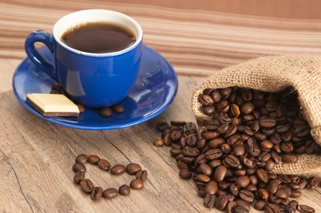 Cup of coffee with beans on old wooden surface photo