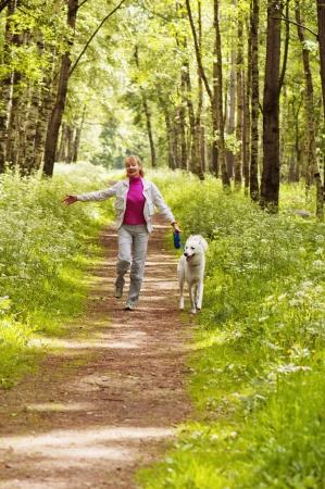 caminar: La mujer camina con un perro en un bosque
