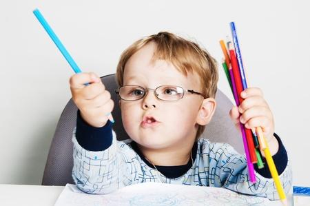 Portrait of the little boy with pencils photo