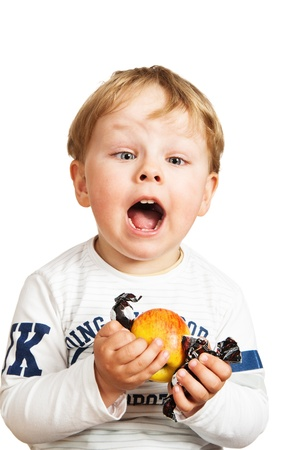 The little boy with an apple and sweets photo