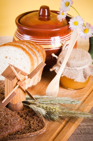 honey, flowers, spike and bread on table photo