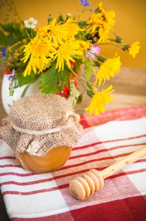 Still life with honeycombs, flowers and pot photo