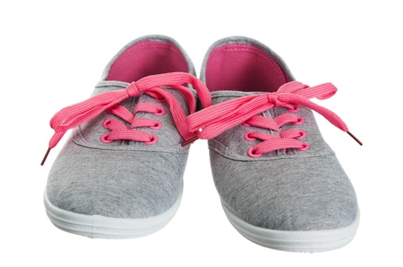 Beautiful female pink sneakers, it is isolated on white photo