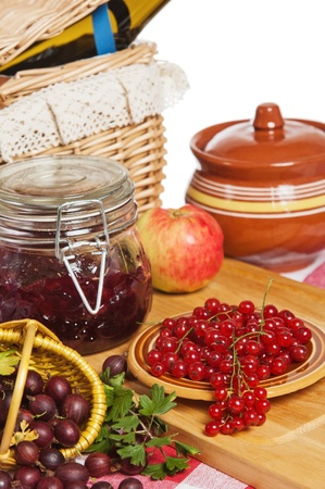 Jam with berries of red currant and gooseberry on the table photo