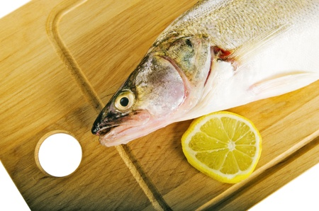Pike perch on a wooden kitchen board, it is isolated on white Stock Photo - 15542211