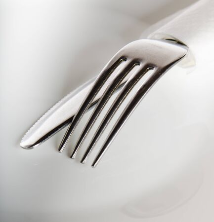 Fork and knife on a white plate photo