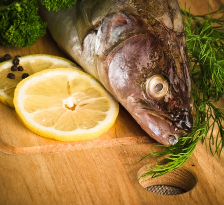 Pike perch on a wooden kitchen board, it is isolated on white Stock Photo - 15563103
