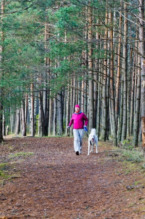 The woman with a dog run in a forest park Stock Photo - 15899951