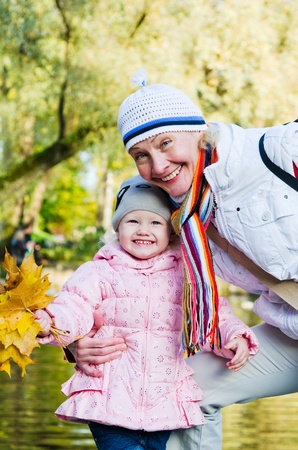 grand daughter: grandmother with the grand daughter in autumn park