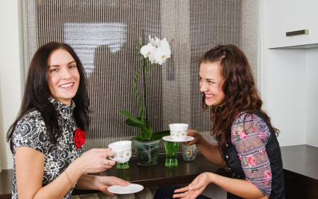 Two young beautiful women drink tea and chat homes photo