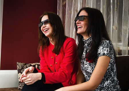 Two beautiful women watching 3D TV at home photo