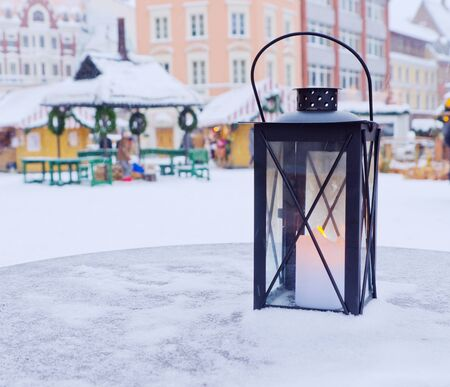 Lantern on a table on a background of the Christmas market photo
