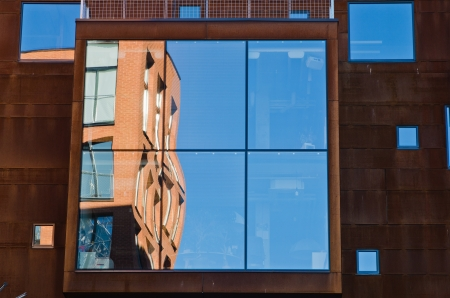 houses and blue sky reflected in windows of modern office building. photo