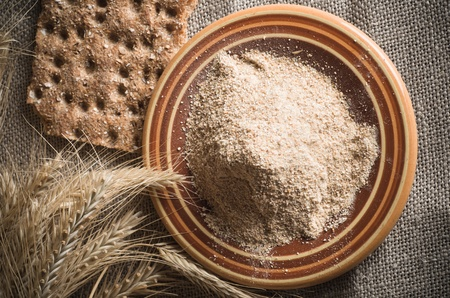Wholemeal flour and wheat on cloth sack, close-up photo
