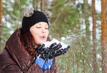 Nette junge Frau spielt mit Schnee im Freien Standard-Bild