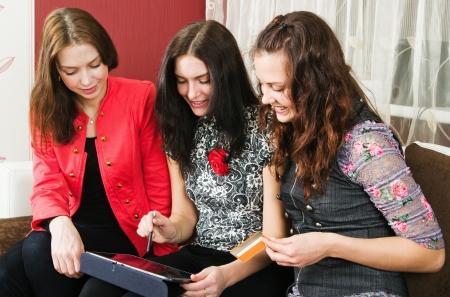 Three beautiful women make purchases on the Internet at home Stock Photo - 17974685