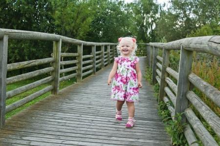 A little girl goes on a wooden bridge photo