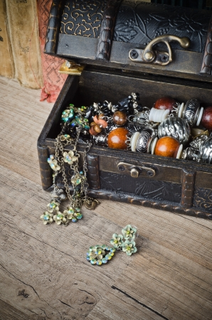 casket with jewelry and old book on a wooden surface photo