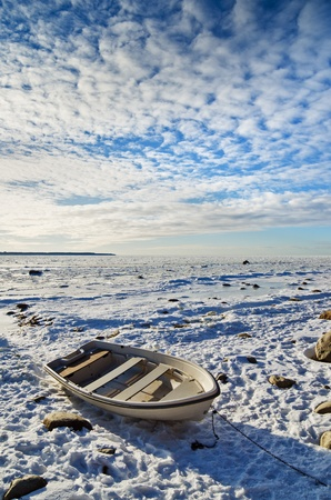 Fishing boat on the sea shore sunny winter afternoon photo