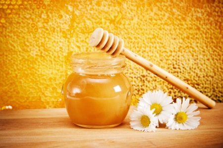 honey cell: Jar of honey and flovers  On the background of honeycombs