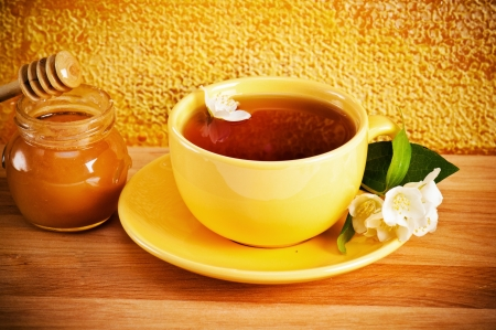 Cup of tea with a flower of a jasmin and honey photo