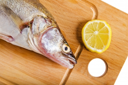 pikeperch: Pike perch on a wooden kitchen board, it is isolated on white Stock Photo