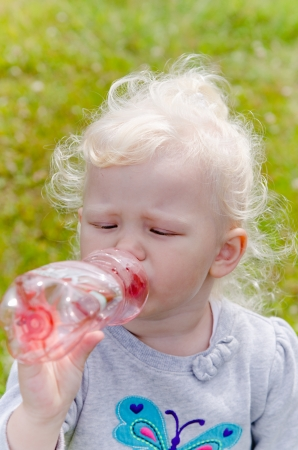 The small blond girl drinks water from a bottle, a close up photo