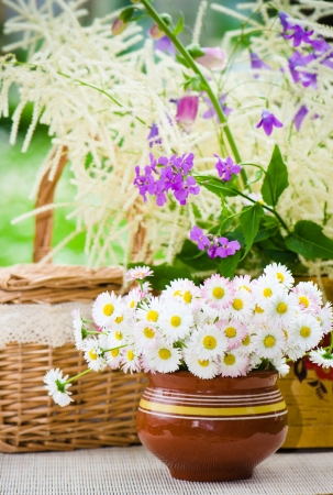 Bouquet of wild flowers in a pot at the table photo